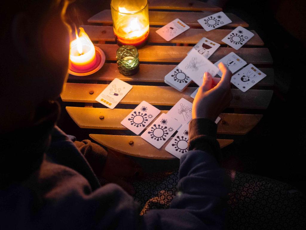 Es ist dunkel. Zwei Personen spielen Karten auf einem Balkon.
