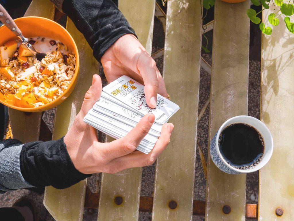 Eine Person mischt das Kartenspiel STOP-CORONA
